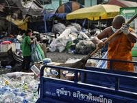 A Buddhist monk sorts salvaged plastic bottles to be recycled into monks' robes and face masks, amid concerns over the spread of the COVID-19 coronavirus, at Wat Chak Daeng Buddhist temple in Samut Prakan on March 23, 2020. The plastic wastes are sent to a separate recycling facility processing it into thread materials and woven as special fabric for monks. Lillian SUWANRUMPHA / AFP
