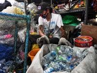 A Buddhist devotee sorts salvaged plastic bottles to be recycled into monks' robes and face masks, amid concerns over the spread of the COVID-19 coronavirus, at Wat Chak Daeng Buddhist temple in Samut Prakan on March 23, 2020. The plastic wastes are sent to a separate recycling facility processing it into thread materials and woven as special fabric for monks. Lillian SUWANRUMPHA / AFP