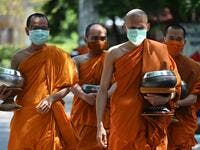 Buddhist monks (back) wear face masks made from recycled plastic bottles, amid concerns over the spread of the COVID-19 coronavirus, at Wat Chak Daeng Buddhist temple in Samut Prakan on March 23, 2020. The plastic wastes are sent to a separate recycling facility processing it into thread materials and woven as special fabric for monks. Lillian SUWANRUMPHA / AFP