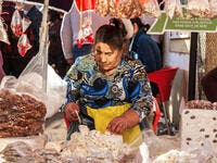 Elderly woman chops blocks of nougat at a market in Portugal (Shutterstock)