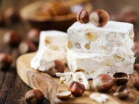 Delicious Italian festive torrone or nougat with hazelnuts on a wood (Shutterstock)