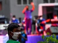 A resident wearing a facemask watches a music band formed by Sri Lankan Navy personnel as they play outside a housing complex during a government-imposed nationwide lockdown as a preventive measure against the COVID-19 coronavirus, in Colombo on April 9, 2020. ISHARA S. KODIKARA / AFP