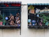 Residents watch from their flats' windows a music band formed by Sri Lankan Navy personnel as they play outside a housing complex during a government-imposed nationwide lockdown as a preventive measure against the COVID-19 coronavirus, in Colombo on April 9, 2020. ISHARA S. KODIKARA / AFP
