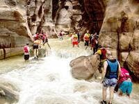 A group of adventurers battle raging waters at Wadi Mujib. (Credit: Wild Jordan)