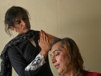 "In this picture taken on May 10, 2020, Julie Khan (L), a member of the transgender community, cuts the hair of Nadeem Kashish at a shelter house in the Bari Imam neighbourhood of Islamabad. Transgender people in the country are known as ""khawajasiras"" or ""hijras"" -- an umbrella term denoting a third sex that includes transgender women and cross-dressers. Pakistan became one of the first countries in the world to legally recognise a third sex in 2009 and began issuing transgender passports from 2017. Aamir Q"
