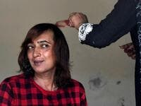 "In this picture taken on May 10, 2020, Nadeem Kashish, a member of the transgender community, gets a haircut at a shelter house in Bari Imam neighbourhood of Islamabad. Transgender people in the country are known as ""khawajasiras"" or ""hijras"" -- an umbrella term denoting a third sex that includes transgender women and cross-dressers. Pakistan became one of the first countries in the world to legally recognise a third sex in 2009 and began issuing transgender passports from 2017. Aamir QURESHI / AFP"