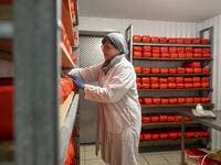"Izabela Ciesielska turns over large blocks of goat cheese in a cold room of the ""Nad Arem"" farm in the Masuria - polish lake region, May 15, 2020. The sheep and cows are in the meadow, the cheese is ripening in a room on the ground floor -- just the kind of scene attracting increasing numbers of Polish cityslickers away from the urban jungle. Wojtek RADWANSKI / AFP"