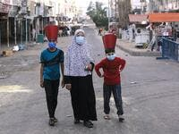 A Palestinian woman and paper-hat-clad children, wearing masks due to the COVID-19 coronavirus pandemic, walk along a street in Gaza City early on May 24, 2020, after performing prayers on the first day of Eid al-Fitr, the Muslim holiday which starts at the conclusion of the holy fasting month of Ramadan. Local authorities in the Hamas-run Palestinian enclave allowed mosques to reopen for Eid al-Fitr as social distancing procedures for the novel coronavirus are maintained while encouraging the elderly to pe