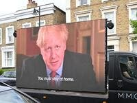 A big screen organised by British political campaign group Led By Donkeys mounted on a vehicle plays a clip from Britain's Prime Minister Boris Johnson's March 23 address to the nation where he explained the stay-at-home coronavirus lockdown rules outside the home of Number 10 Downing Street special advisor Dominic Cummings in London on May 24, 2020 following allegations Cummings broke coronavirus lockdown rules by travelling across the country in March. British Prime Minister Boris Johnson was under increa