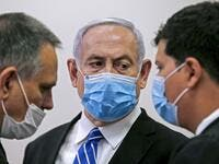 Israeli Prime Minister Benjamin Netanyahu (C), wearing a protective face maks, speaks with his lawyer inside a courtroom at the district court of Jerusalem on May 24, 2020, during the first day of his corruption trial. Fresh from forming a new government after more than 500 days of electoral deadlock, Netanyahu is expected to begin a new battle in the Jerusalem District Court -- to stay out of prison. The 70-year-old was scheduled to appear at a court hearing to formally confirm his identity to judges, afte