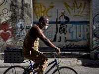 A man wears a face mask as he rides a bicycle in Havana, on May 25, 2020. Cuba reported 1947 confirmed cases of COVID-19 and 82 deceased due to the virus. YAMIL LAGE / AFP