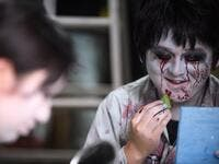 This picture taken on June 15, 2020 shows actor Kenta Iwana (R), 25, putting on zombie makeup before a demonstration of a drive-in haunted house at a garage in Tokyo. A car horn beeps and the horror begins: a bloody murder and rampaging zombies. But this drive-in haunted house in Japan protects against the most terrifying enemy of all -- coronavirus. Inside a car, guests can scream as loudly as they like, with no mask required, as hideous creatures daubed in blood swarm towards them.  Philip FONG / AFP