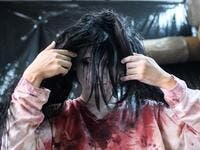 This picture taken on June 15, 2020 shows actress Ayaka Imaide, 34, putting on zombie makeup before a demonstration of a drive-in haunted house at a garage in Tokyo. A car horn beeps and the horror begins: a bloody murder and rampaging zombies. But this drive-in haunted house in Japan protects against the most terrifying enemy of all -- coronavirus. Inside a car, guests can scream as loudly as they like, with no mask required, as hideous creatures daubed in blood swarm towards them.  Philip FONG / AFP