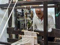 Muhammad Saud, a 65-year-old Syrian silk farmer, handweaves silk threads on a loom at his home workshop in the village of Deir Mama, in west-central Syria on June 22, 2020. MAHER AL MOUNES / AFP