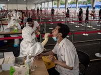 This file photo taken on June 24, 2020 shows a health worker (L, front) wearing a protective suit, face mask and face shield takes a swab test on a man at an outdoor area during a mass testing for the COVID-19 coronavirus at the Jinrong Street testing site in Beijing.NICOLAS ASFOURI / AFP