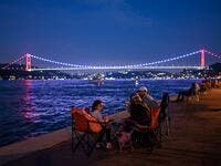 People enjoy the evening as they sit next to the shore of the Bosphorus as Fatih Sultan Mehmet bridge is seen in the backround on July 6, 2020 in Istanbul. Ozan KOSE / AFP