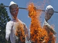 "Palestinian supporters of al-Ahrar movement burn effigies depicting (L to R) US President Donald Trump, Trump's Middle East peace plan dubbed as the ""Deal of the Century"", and Israeli Prime Minister Benjamin Netanyahu, during a demonstration against Israel's plans to annex parts of the occupied West Bank, in Rafah in the southern Gaza Strip on July 7, 2020. Mohammed ABED / AFP"