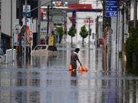 A worker wades through flood waters as he delivers gas bottles in Kurume, in Fukuoka Prefecture on July 8, 2020. Japan will deploy more troops to search for survivors of devastating floods and landslides that have killed at least 52 people in the southwest of the country, Prime Minister Shinzo Abe pledged CHARLY TRIBALLEAU / AFP