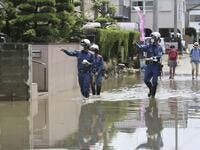 Fire brigade officers check on residents following heavy rain in Omuta, Fukuoka Prefecture on July 8, 2020. Torrential rain pounded central Japan on July 8 as authorities said 58 people were feared dead in days of heavy downpours that have triggered devastating landslides and terrifying floods. STR / JIJI PRESS / AFP