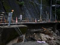 A man walks along a road damaged from recent heavy rains and flooding in the village of Kuma, Kumamoto prefecture on July 9, 2020. Japanese emergency services and troops were scrambling on July 9 to reach thousands of homes cut off by catastrophic flooding and landslides that have killed dozens and caused widespread damage. CHARLY TRIBALLEAU / AFP