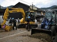 Workers clear debris and mud outside homes following heavy rains and flooding in the village of Gero, Gifu prefecture on July 9, 2020. Japanese emergency services and troops were scrambling to reach thousands of homes cut off by devastating flooding and landslides that have killed dozens and caused widespread damage. Philip FONG / AFP