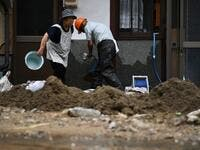 People clear debris and mud outside their home following heavy rains and flooding in the village of Gero, Gifu prefecture on July 9, 2020. Japanese emergency services and troops were scrambling to reach thousands of homes cut off by devastating flooding and landslides that have killed dozens and caused widespread damage. Philip FONG / AFP