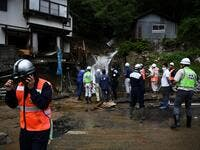 Government officials look at a damaged home following heavy rains and flooding in the village of Gero, Gifu prefecture on July 9, 2020. Japanese emergency services and troops were scrambling to reach thousands of homes cut off by devastating flooding and landslides that have killed dozens and caused widespread damage. Philip FONG / AFP