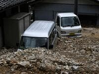 Damaged vehicles are seen under rocks from a mudslide following heavy rains and flooding in the village of Gero, Gifu prefecture on July 9, 2020. Japanese emergency services and troops were scrambling to reach thousands of homes cut off by devastating flooding and landslides that have killed dozens and caused widespread damage. Philip FONG / AFP
