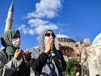 Women pray outside the Hagia Sophia museum on July 10, 2020 in Istanbul as people gather to celebrate after a top Turkish court revoked the sixth-century Hagia Sophia's status as a museum, clearing the way for it to be turned back into a mosque. The Council of State, the country's highest administrative court which on July 2 debated a case brought by a Turkish NGO, cancelled a 1934 cabinet decision and ruled the UNESCO World Heritage site would be reopened to Muslim worshipping. The sixth-century Istanbul b