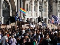 A protester (L) waves a rainbow flag, symbol of LGBTQ social movements, and others hold placards during a demonstration called by feminist movements in front of the city hall in Paris, on July 10, 2020, to denounce the nomination of French Interior Minister, facing rape accusations and French Justice Minister who criticised the #MeToo movement against sexual harassment. Thomas COEX / AFP