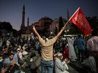 A man flashes the V for Victory hand sign and waves a flag outside the Hagia Sophia museum in Istanbul on July 10, 2020 as people gather to celebrate after a top Turkish court revoked the sixth-century Hagia Sophia's status as a museum, clearing the way for it to be turned back into a mosque. The Council of State, the country's highest administrative court which on July 2 debated a case brought by a Turkish NGO, cancelled a 1934 cabinet decision and ruled the UNESCO World Heritage site would be reopened to