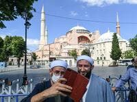 "Two men take a selfie picture in front of Hagia Sophia on July 11, 2020 in Istanbul, a day after a top Turkish court revoked the sixth-century Hagia Sophia's status as a museum, clearing the way for it to be turned back into a mosque. The World Council of Churches, which represents 350 Christian churches, said on July 11 it wrote to Turkey's President expressing ""grief and dismay"" over his decision to turn the Hagia Sophia back into a mosque. Ozan KOSE / AFP"