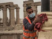 A municipality worker cleans lamp posts amid coronavirus fears outside the Luxor Temple, March 12, 2020. (AFP)