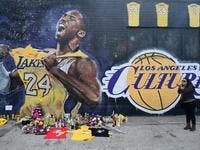 French national and longtime US resident Natalie Burle blows a kiss in direction of Kobe Bryant mural in downtown Los Angeles / © AFP