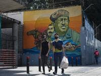 People wearing protective masks walks past a mural depicting Venezuela's late President Hugo Chavez, in downtown Caracas on July 28, 2020, after the government intensified a nationwide lockdown as a preventive measure against the spread of COVID-19. Federico PARRA / AFP