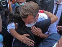 A Lebanese youth hugs French President Emmanuel Macron during a visit to the Gemmayzeh neighbourhood, which has suffered extensive damage due to a massive explosion in the Lebanese capital, on August 6, 2020. French President Emmanuel Macron visited shell-shocked Beirut, pledging support and urging change after a massive explosion devastated the Lebanese capital in a disaster that has sparked grief and fury. AFP