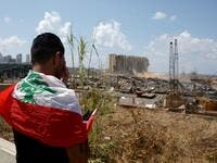 A man draped in a Lebanese flag reacts as he stands before the ravaged port of Lebanon's capital Beirut on August 9, 2020, in the aftermath of a colossal explosion that occurred days prior due to a huge pile of ammonium nitrate that had languished for years at a port warehouse. The huge chemical explosion that hit Beirut's port, devastating large parts of the Lebanese capital and claiming over 150 lives, left a 43-metre (141 foot) deep crater, a security official said. The blast Tuesday, which was felt acro