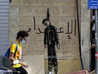 "A Lebanese volunteer walks past graffiti depicting a hanged politician with the word ""execution"", in the devastated Beirut neighbourhood of Gemmayzeh, on August 11, 2020, following a huge chemical explosion that ravaged large parts of the capital. JOSEPH EID / AFP"