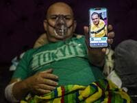 Venezuelan Wilmer Hernandez, 44, shows a picture of his father Wilmer Arcadio Hernandez, 63, as he remains connected to an oxygen tank in his home in Villa Maria del Triunfo, south of Lima, Peru, on June 25, 2020. Global deaths from the coronavirus have almost reached on September 25, 2020 the grim threshold of one million. Around one-third of fatalities were in Latin America, where countries with overstretched medical resources are preparing for a further onslaught. ERNESTO BENAVIDES / AFP