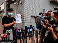 Pro-democracy activist Joshua Wong speaks to the media while holding up a bail document after leaving Central police station in Hong Kong on September 24, 2020. (AFP/File Photo)