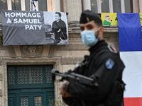 A French police officer stands next to a portrait of French teacher Samuel Paty on display on the facade of the Opera Comedie in Montpellier on October 21, 2020, during a national homage to the teacher who was beheaded for showing cartoons of the Prophet Mohamed in his civics class. France pays tribute on October 21 to a history teacher beheaded for showing cartoons of the Prophet Mohamed in a lesson on free speech, an attack that has shocked the country and prompted a government crackdown on radical Islam.