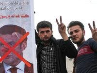 Men flash the victory gesture as they pose for a picture next to a sign condemning French President Emmanuel Macron, and depicting him with a pig snout, for his comments over Prophet Mohammed cartoons in Syria's rebel-held northwestern city of Idlib on October 25, 2020. OMAR HAJ KADOUR / AFP
