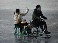 A family use mobile phone to take a selfie as they ride sled on a frozen lake in Beijing on January 12, 2021. WANG Zhao / AFP