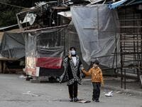 A mask-clad woman and boy walk past shuttered shops and stalls in Souk Sabra in the southern suburbs of the Lebanon's capital Beirut on January 16, 2021, despite a national total lockdown as a measure against the COVID-19 coronavirus pandemic. ANWAR AMRO / AFP