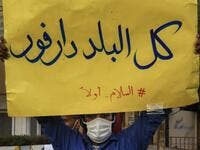 "In this file photo taken on July 4, 2020, A mask-clad demonstrator (due to the COVID-19 coronavirus pandemic) stands with a sign reading in Arabic ""all of the country is Darfur, #PeaceFirst"", during a protest outside the Sudanese Professionals Association in the Garden City district of Sudan's capital Khartoum, in solidarity with the people of the Nertiti region of Central Darfur province in the country's southwest. ASHRAF SHAZLY / AFP"