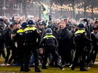 Hundreds of protestors not wearing face masks clash with Dutch riot police at an illegal protest against the Netherlands' new lockdown measures in Museumplein today. (AFP)