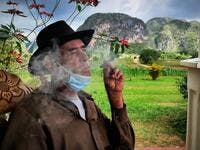 Eduardo Hernandez, owner of a private restaurant and a tobacco cultivator, smokes a cigar in his house in Vinales, Cuba, on January 28, 2021. At the foot of the majestic rock formations of Vinales, the terraces of the restaurants look empty and the lodgings have closed. With the arrival of COVID-19, the incipient prosperity of this Cuban town came to a halt and people abandoned tourism jobs to return to work the land. YAMIL LAGE / AFP