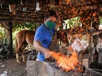 Yusmani Garcia, a blacksmith and tour guide, makes a horseshoe at his house in Vinales, Cuba, on January 28, 2021. At the foot of the majestic rock formations of Vinales, the terraces of the restaurants look empty and the lodgings have closed. With the arrival of COVID-19, the incipient prosperity of this Cuban town came to a halt and people abandoned tourism jobs to return to work the land. YAMIL LAGE / AFP