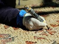 A worker employed by a pilot project run by the UN cultural agency UNESCO, restores a mosaic floor at an ancient church complex, in the small town of Rihab, some 70 kilometres north of the Jordanian capital Amman, on February 9, 2021. In the ruins of the ancient Byzantine church in Jordan, local townspeople and Syrian refugees work side by side on a project that unites preserving cultural heritage and fighting poverty.  Khalil MAZRAAWI / afp