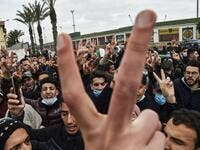 "Policemen are seen on the sidelines as students chant slogans while demonstrating in the centre of Algeria's capital Algiers on February 23, 2021 a day after the second anniversary of the ""Hirak"" protest movement. The ""Hirak"" protest movement in April 2019 forced longtime president Abdelaziz Bouteflika into resigning. Police were deployed in force in Algiers, with security checkpoints and identity checks carried out around key flashpoints, while helicopters hovering overhead. RYAD KRAMDI / AFP"